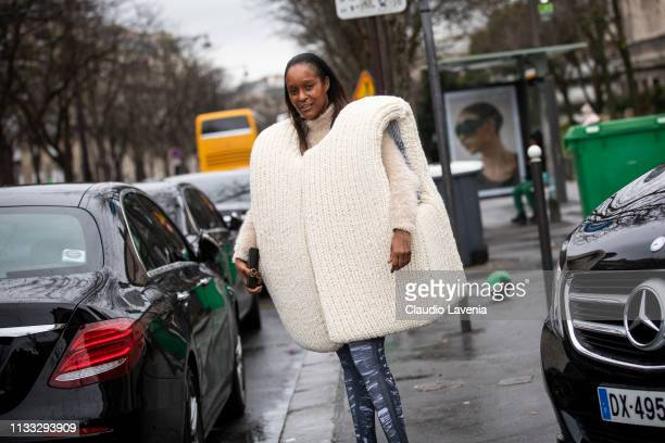 Michelle Elie wearing a knitted oversized vest cream jumper and grey printed leggings is seen outside Haider Ackermann on Day 6 Paris Fashion Week...