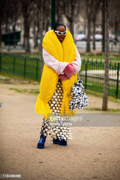 Michelle Elie wearing a lilac jumper big yellow scarf sequins maxi skirt blue shoes sequins bag and pink fur gloves is seen outside Chanel on Day 9...