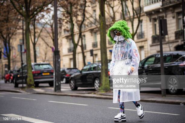 Michelle Elie wearing a long see through jacket with green fur details and black and white Nike sneakers is seen in the streets of Paris before the...