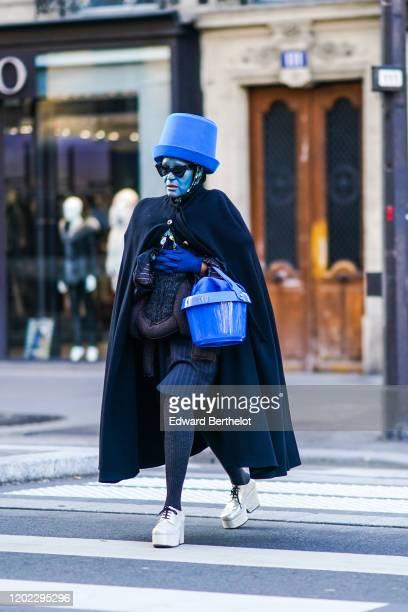 Michelle Elie wears a blue large hat shaped as a bucket, a long cape, a blue plastic bucket, gray wool leggings, white platform shoes, blue face...