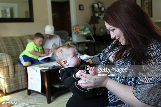 Michelle Frigon plays with her newborn son Charlie 3 months while her older son Billy reads with his grandpa in Millbury MA on Jun 5 2015 Michelle...