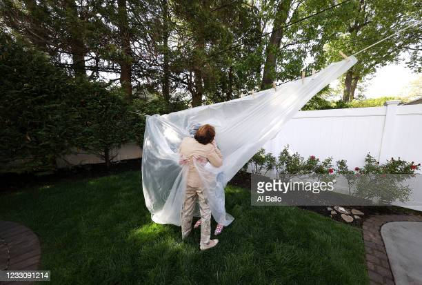 Michelle Grant hugs her Mother Mary Grace Sileo through a plastic drop cloth hung up on a homemade clothes line during Memorial Day Weekend on May 24...