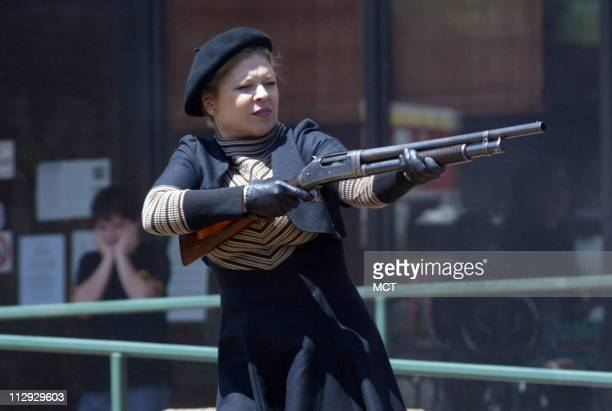 Michelle Groves, of Dallas, plays the role of Bonnie Parker during a reenactment of a bank robbery gunfight at this year's Bonnie & Clyde Festival on...