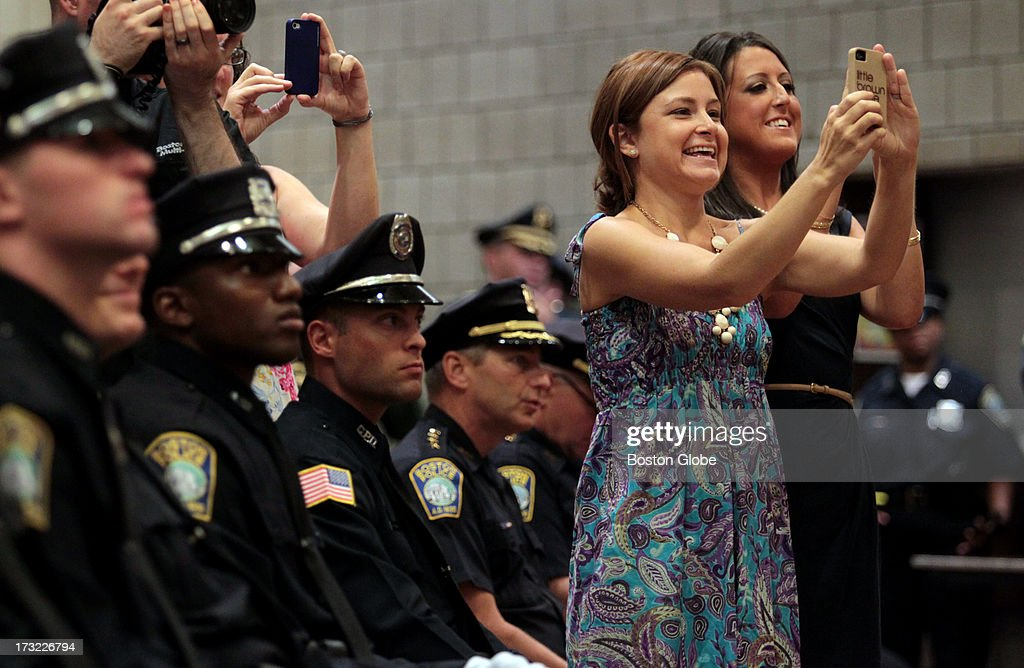Michelle Hill and Nicole Kennedy take pictures of their brother Gerard Kennedy during his graduation ceremony from the Boston Police Academy at the I.B.E.W. Hall on Freeport Street in Dorchester.