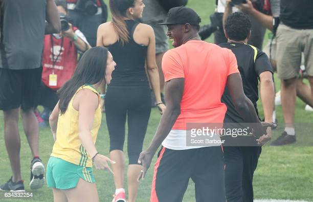 Michelle Jenneke of Australia gestures to Usain Bolt of Usain Bolt's AllStar team as the teams run onto the track during the 2017 Nitro Athletics...