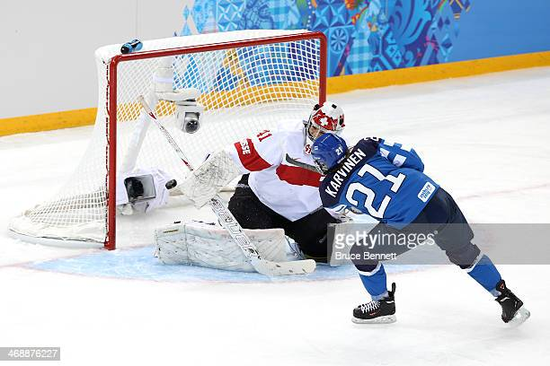 Michelle Karvinen of Finland scores a goal against Florence Schelling of Switzerland in the first period during the Women's Ice Hockey Preliminary...