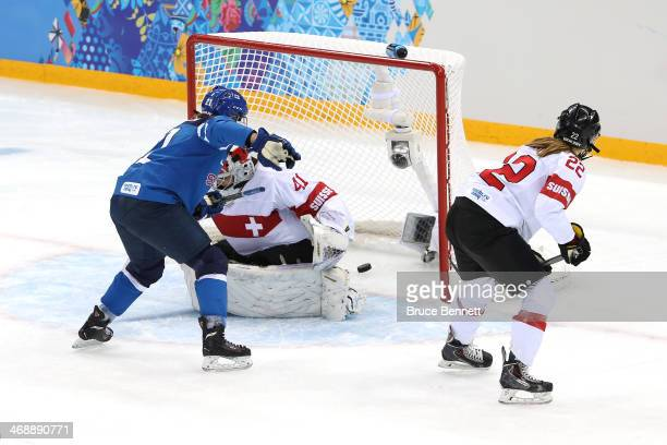 Michelle Karvinen of Finland scores a goal in the second period against Florence Schelling of Switzerland during the Women's Ice Hockey Preliminary...