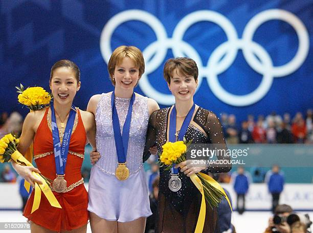 US Michelle Kwan US gold medalist Sarah Hughes and Russian silver medalist Irina Slutskaya smile on the podium after the women's figure skating event...