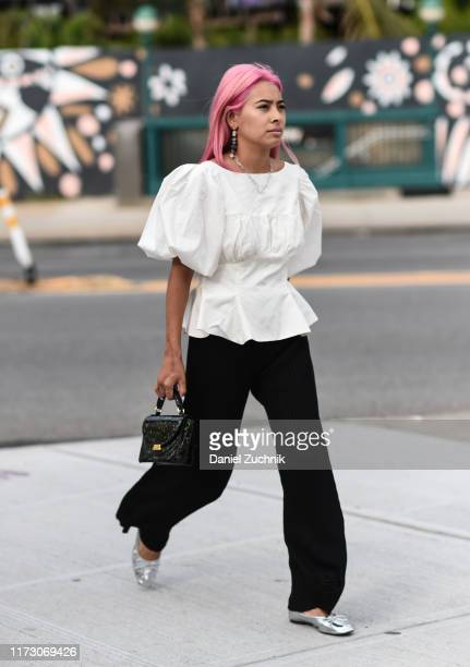 Michelle Li is seen wearing a white top and black pants and purse outside the Area show during New York Fashion Week S/S20 on September 07 2019 in...