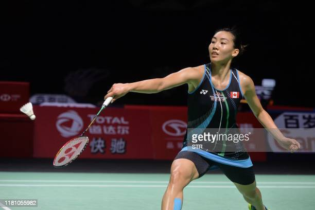 Michelle Li of Canada hits a return against Chen Yufei of China during their women's singles semifinal match at the Fuzhou China Open badminton...