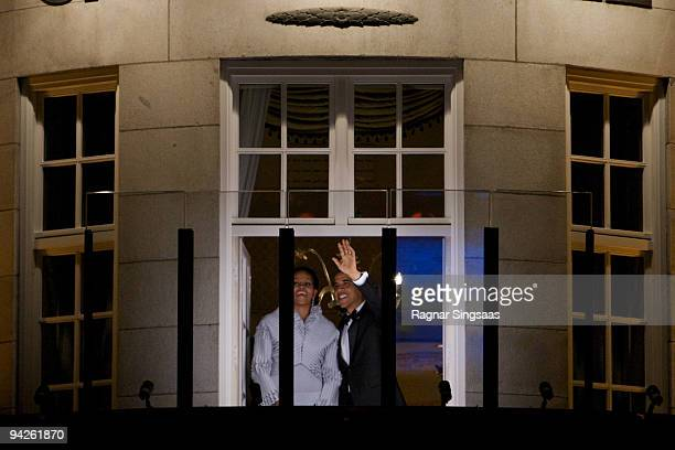 Michelle Obama and Barack Obama wave to crowds from behind bullet proof glass on the balcony of the Grand Hotel on December 10 2009 in Oslo Norway