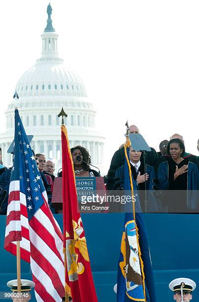 Michelle Obama listens as Millicent Scarlett sings the National Anthem during the 2010 George Washington University commencement at the National Mall...