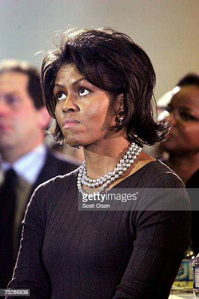 Michelle Obama wife of Senator Barack Obama listen to her husband address a crowd gathered for a campaign rally at Central Middle School February 10...
