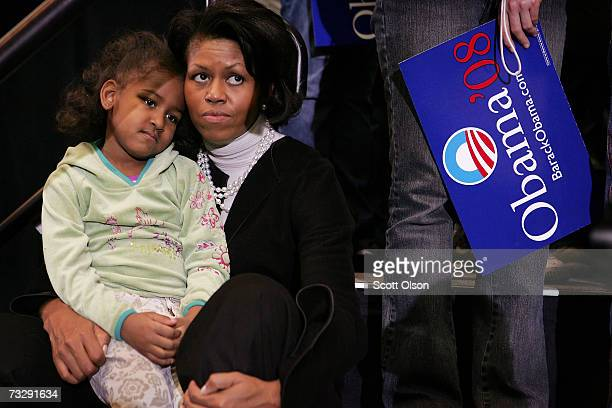 Michelle Obama, wife of Senator Barack Obama , listens with her daughter Sasha as the Senator addresses a crowd gathered at a campaign rally at Iowa...