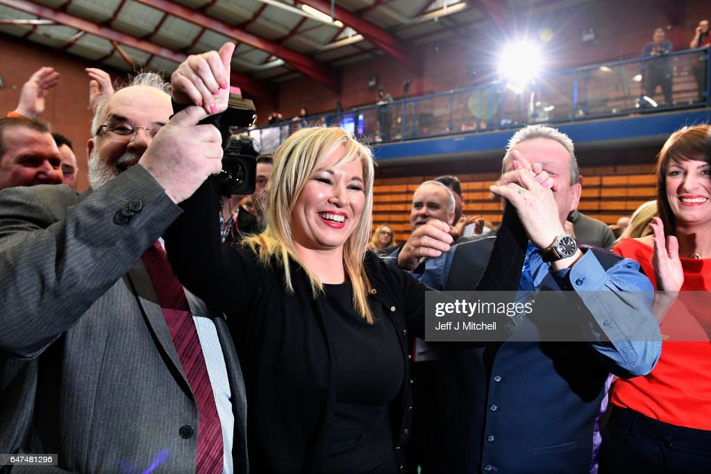 Michelle O'Neill, leader of Sinn Fein in Northern Ireland (C) celebrates winning her seat for Mid Ulster while surrounded by Francie Molloy, (L) and Ian Milne (R) at the Seven Towers Leisure Centre count in the Northern Ireland assembly election on March 3, 2017 in Ballymena, Northern Ireland. A snap election was called following the resignation of the Deputy First Minister Martin McGuiness, with indications showing that voter turnout yesterday was considerably higher than in May last year. The first declarations are expected around lunchtime today.