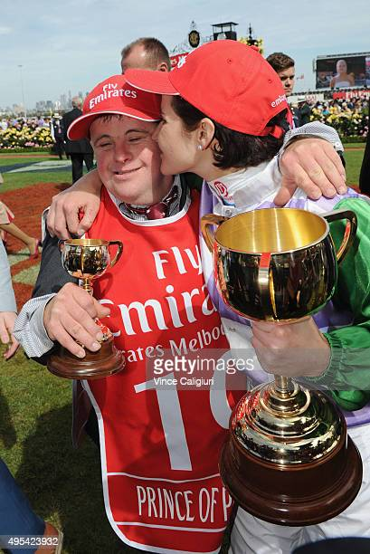 Michelle Payne kisses brother Stephen Payne and poses with the trophy after riding Prince of Penzance to win race 7 the Emirates Melbourne Cup on...