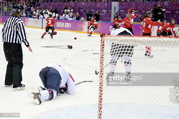 Michelle Picard of the USA falls to the ice as Canada celebrates the gamewinning goal by MariePhilip Poulin during the overtime period of Canada's 32...