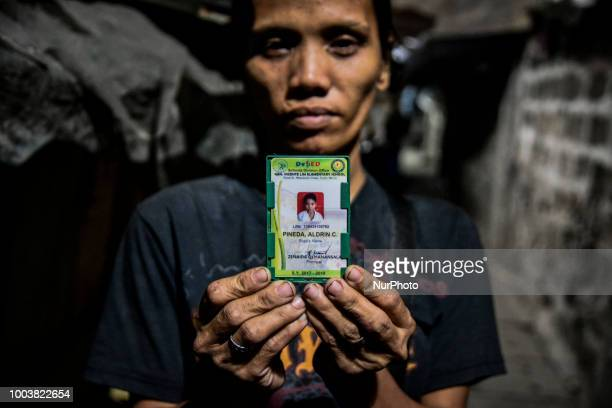 Michelle Pineda holds the school ID of her 13yearold son Aldrin who was shot to death by a police officer at his funeral wake in Manila Philippines...