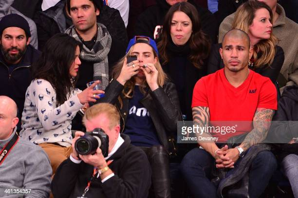 Michelle Rodriguez Cara Delevingne and Miguel Cotto attend the Detroit Pistons vs New York Knicks game at Madison Square Garden on January 7 2014 in...