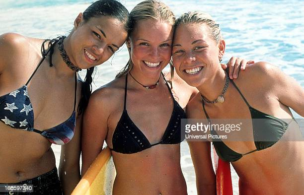 Michelle Rodriguez Kate Bosworth and Sanoe Lake just out of the water with their surf boards arm and arm smiling in a scene from the film 'Blue...