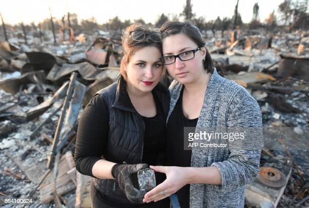 Michelle Ross and Stephanie Staykow pose for a photo while holding their baptism crosses they found in the remains of their burned home in Santa Rosa...