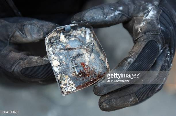 Michelle Ross shows her baptism cross that she found in the remains of her burned home in Santa Rosa California on October 20 2017 Residents are...