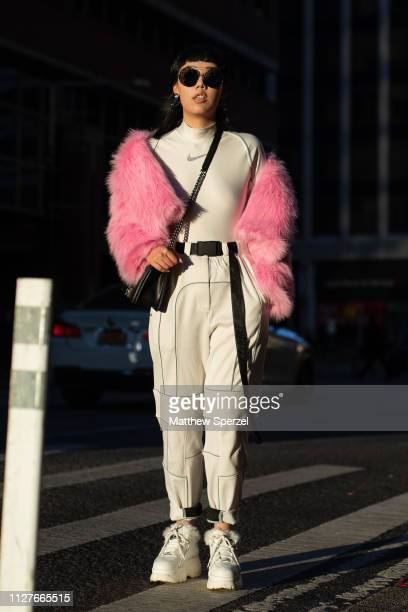 Michelle Song is seen on the street during Men's New York Fashion Week wearing pink fur coat with Nike spandex top and black bag with white tech...