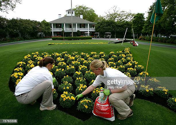 Michelle Stevens and Anna Yeager work on a flowerbed in front of the clubhouse prior to the start of The Masters at the Augusta National Golf Club on...