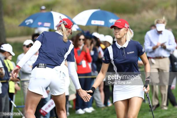 Michelle Wie and Jessica Korda of the United States low five on the eighth green in the Pool B match between United States and Sweden on day one of...
