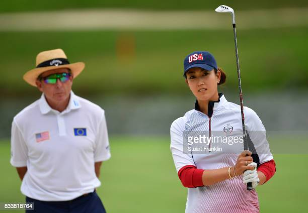 Michelle Wie of Team USA plays a shot whilst being watched by coach David Leadbetter during practice prior to The Solheim Cup at Des Moines Golf and...