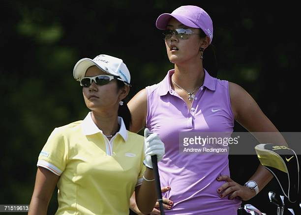 Michelle Wie of the United States and Ai Miyazato of Japan wait on the fourth hole during the first round of the Evian Masters on July 26 2006 in...