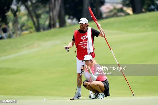Michelle Wie of the United States and hr caddie line up her putt for birdie on her way to winning during the final round of the HSBC Women's World...