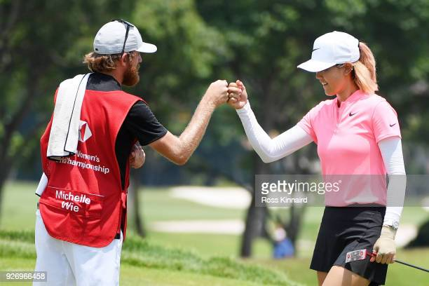 Michelle Wie of the United States celebrates with her caddie on the 18th green during the final round of the HSBC Women's World Championship at...