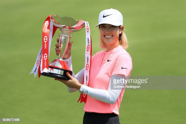 Michelle Wie of the United States celebrates with the winner's trophy after the final round of the HSBC Women's World Championship at Sentosa Golf...