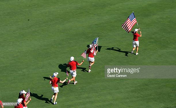 Michelle Wie of the USA leads a string of victorious USA players down the 18th fairway as they celebrate their team's victory during the Sunday...
