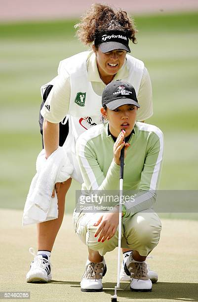 Michelle Wie of the USA lines up a putt with her caddie Fanny Sunesson on the second hole during the final round of the Safeway International at...