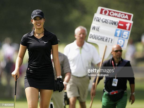 Michelle Wie of USA smiles as she approaches the ninth green with a scoreboard carrier behind her during the second round of the Omega European...