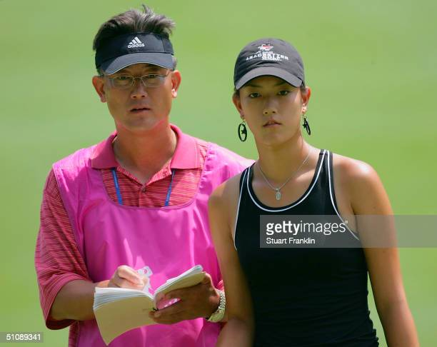 Michelle Wie of USA with her father and caddie BJ Wie on the 18th hole during the first round at The Evian Masters at Evian Golf Club on July 21 2004...