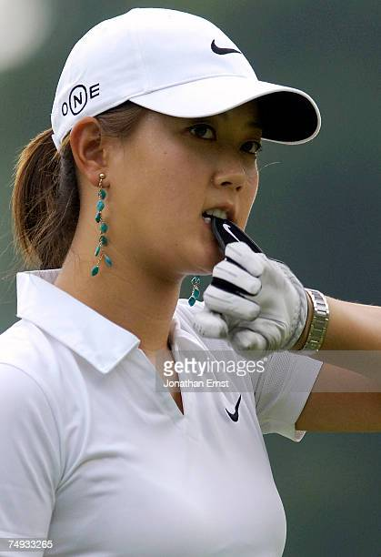 Michelle Wie removes her glove on the 18th green during a practice round prior to the start of the US Women's Open Championship at Pine Needles Lodge...