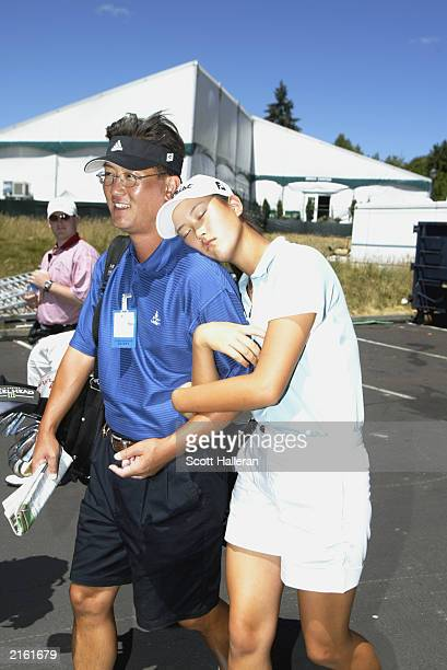 Michelle Wie walks out of the media center with her father/caddie BJ Wie during practice for the US Women's Open at Pumpkin Ridge Golf Club on July 2...