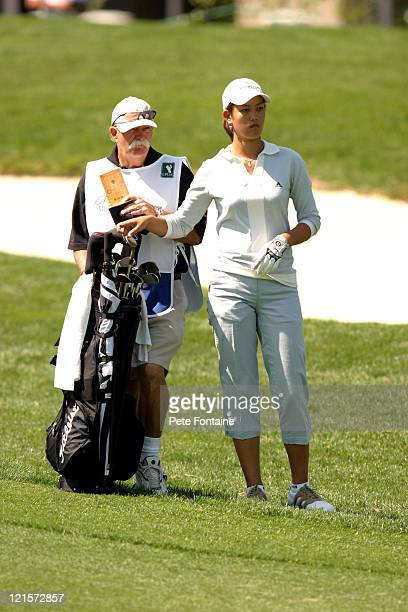 """Michelle Wie with caddie Mike """"Fluff"""" Cowan on the 11th hole during the first round at the Michelob Ultra Open, May 6, 2004."""