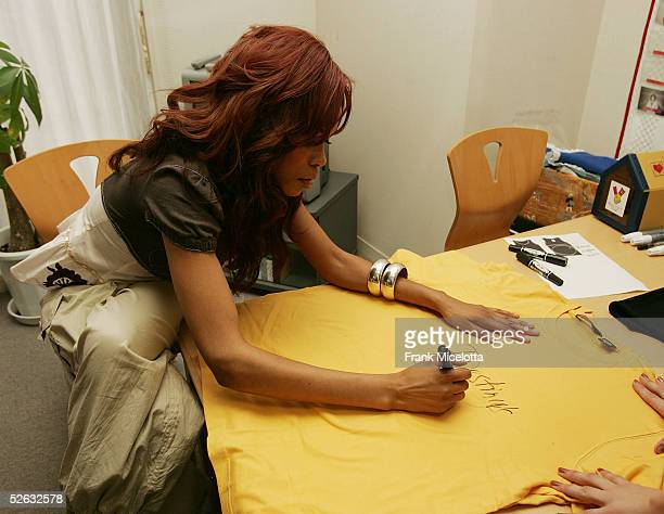 Michelle Williams of Destiny's Child signs gifts during the bands visit to the Ronald McDonald House April 13 2005 in Setagaya district of Tokyo...
