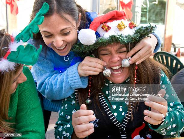 Michelle Wulkowicz center causes her friend Christine Lyng right to burst in to laughter when she pushes the Christmas ornaments into her face at the...