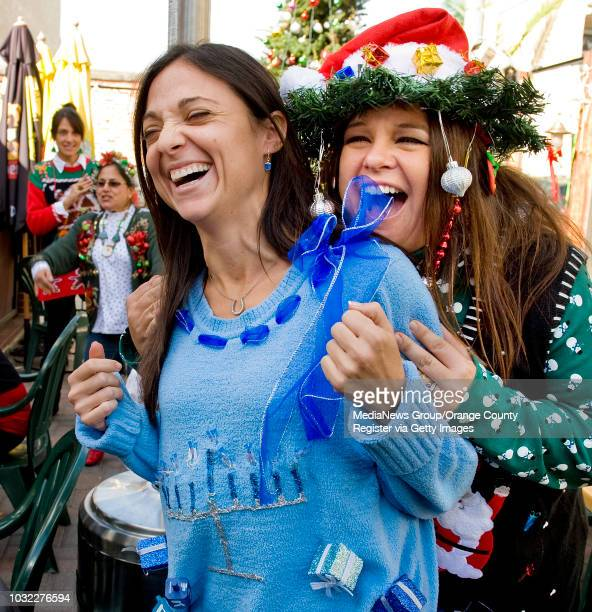 Michelle Wulkowicz left wearing a Menorah sweater that lights up shares a laugh with Christine Lyng right at the 2nd Annual Ugly Christmas Sweater...