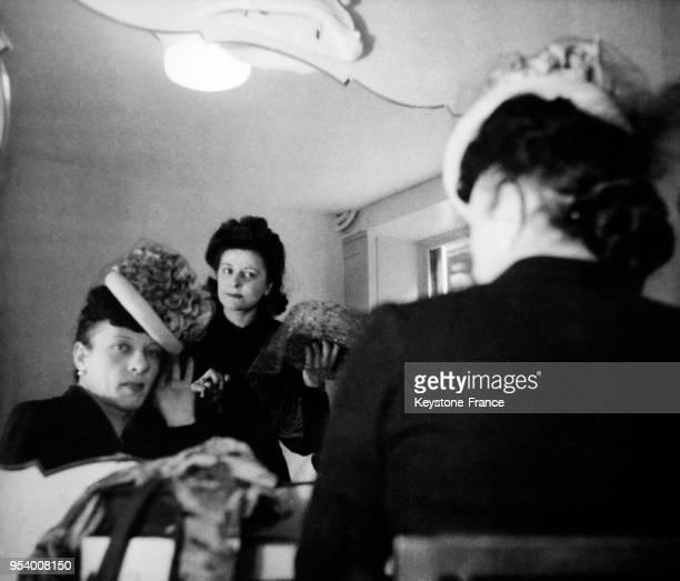 MichelMarie Poulain essayant un chapeau chez une modiste à Paris France circa 1940