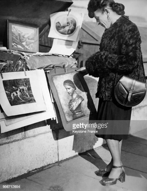 MichelMarie Poulain examinant une peinture chez un bouquiniste des quais de Seine à Paris France circa 1940