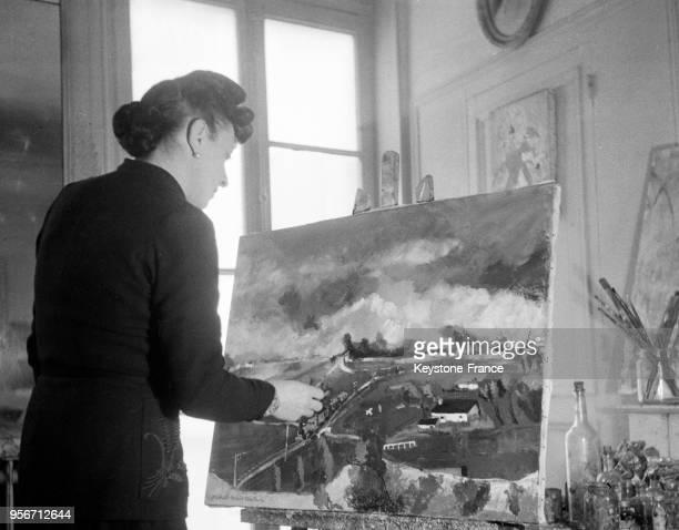 MichelMarie Poulain hommefemme peintre donne une dernière retouche à l'un de ses tableaux dans son atelier à Paris France en 1946