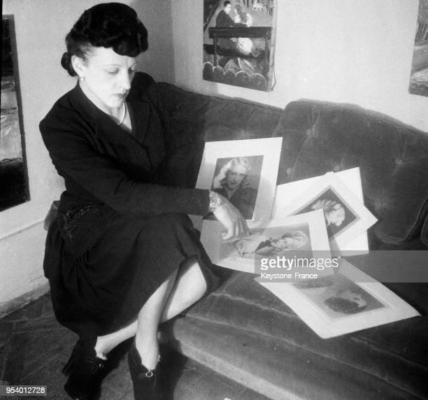 MichelMarie Poulain hommefemme peintre regarde différents portraits qu'il a fait dans son atelier à Paris France en 1946