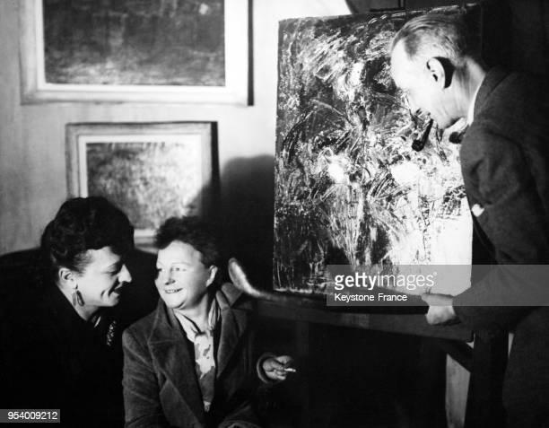 MichelMarie Poulain à la Galerie Cardon avec les propriétaires monsieur et madame Cardon à Paris France circa 1940
