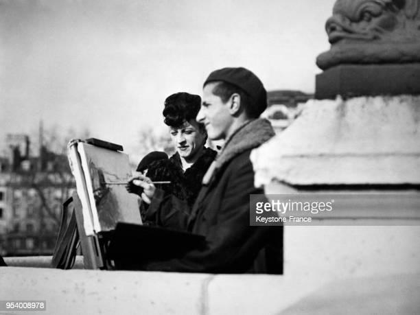 MichelMarie Poulain regardant peindre une jeune artiste sur les quais de Seine à Paris France circa 1940